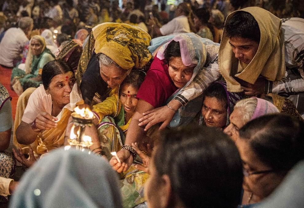 6.INDIE, Waranasi, 11 maja 2014: Wierni starają się dotknąć ognia rozpalonego nad brzegami Gangesu. (Foto: Kevin Frayer/Getty Images)