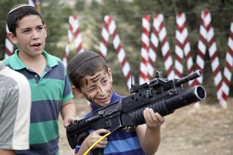 7.ZACHODNI BRZEG, Efrat, 6 maja 2014: Izraelski chłopiec bawi się karabinem M-16. AFP PHOTO/GALI TIBBON