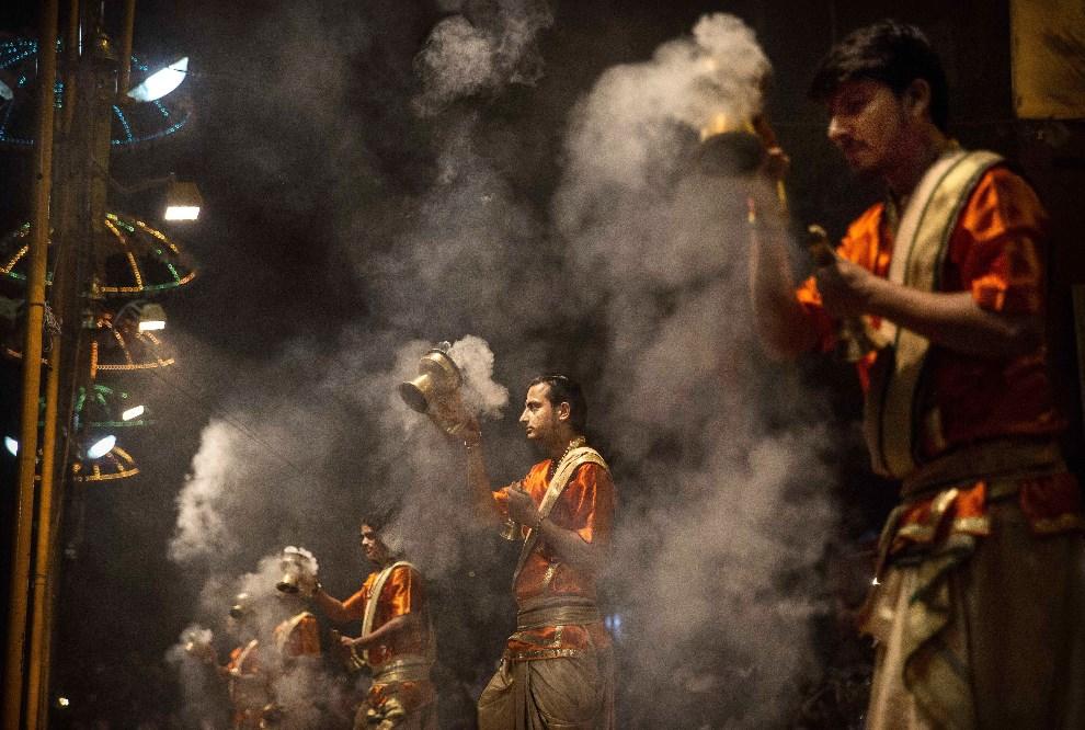 7.INDIE, Waranasi, 11 maja 2014: Kapłani uczestniczący w arati – rytuale, w którym światło lampek ofiarowane jest bóstwu. (Foto: Kevin Frayer/Getty Images)