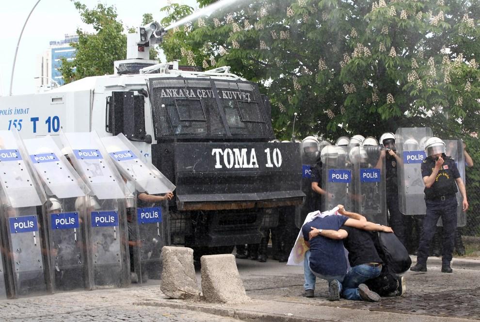 8.TURCJA, Ankara, 14 maja 2014: Uczestnicy protestów przeciw złym warunkom pracy w kopalniach, klęczą przed armatką wodną.. AFP PHOTO / ADEM ALTAN
