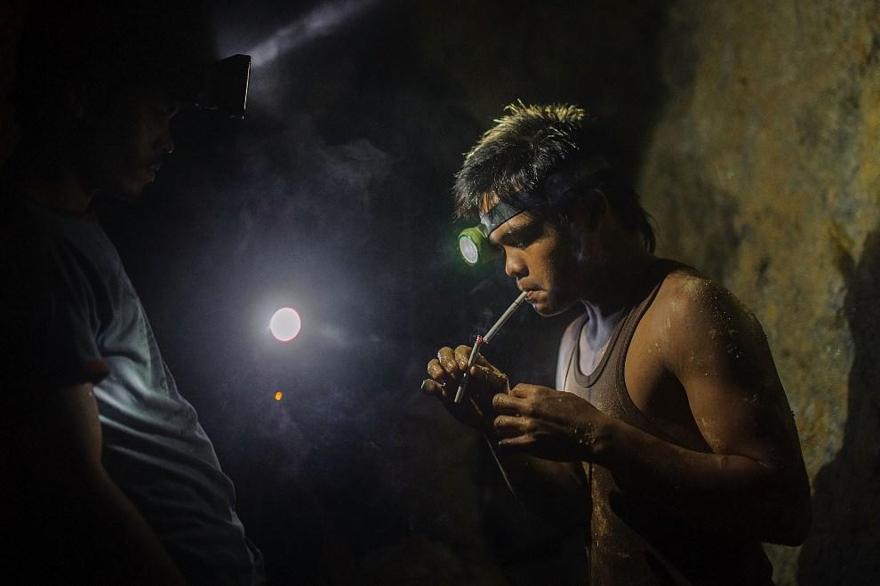 8.FILIPINY, Pinut-An, 22 kwietnia 2014: Górnik odpalający papierosa. (Foto: Luc Forsyth/Getty Images)