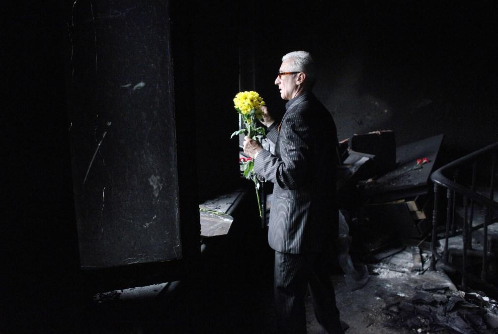 9.UKRAINA, Odessa, 4 maja 2014: Mężczyzna z kwiatami wewnątrz spalonego budynku. AFP PHOTO / ANATOLII STEPANOV
