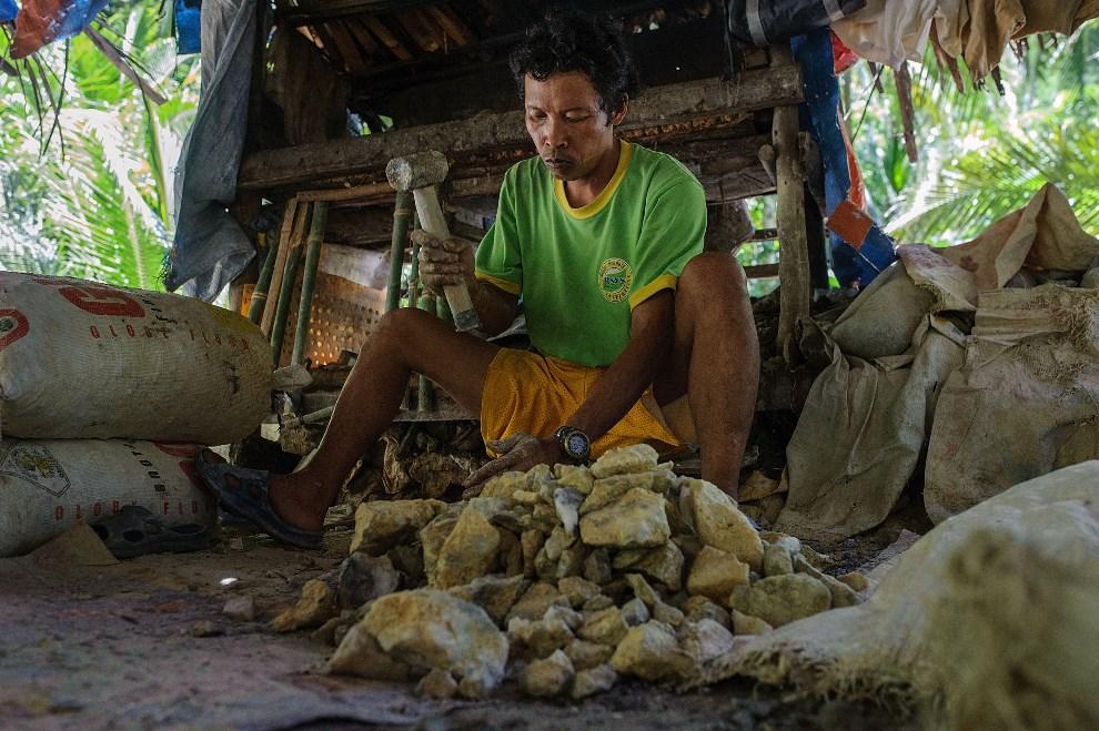 9.FILIPINY, Pinut-An, 22 kwietnia 2014: Mężczyzna rozbija urobek na mniejsze, łatwiejsze w obróbce, kawałki. (Foto: Luc Forsyth/Getty Images)