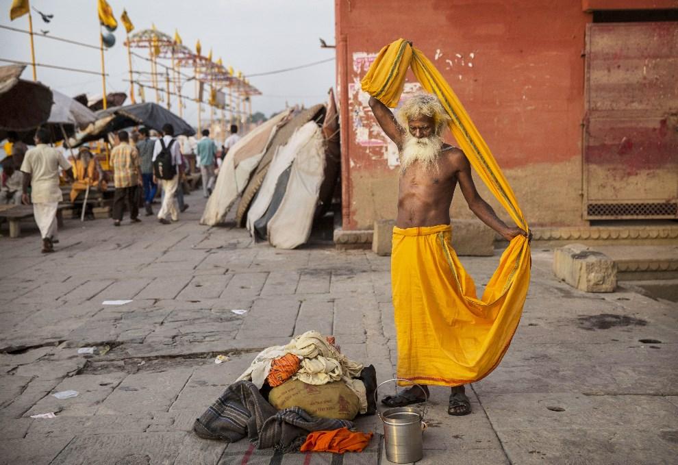 9.INDIE, Waranasi, 11 maja 2014: Sadhu ubiera się po zakończonej kąpieli w Gangesie. (Foto: Kevin Frayer/Getty Images)