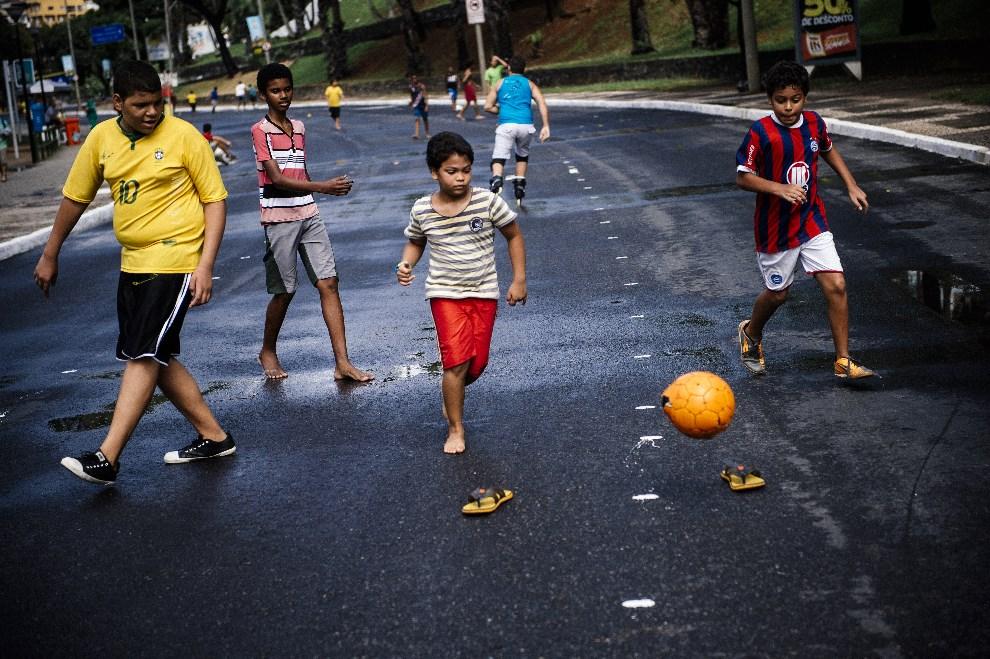 10.BRAZYLIA, Salvador, 8 czerwca 2014: Chłopcy grający w piłkę w pobliżu Fonte Nova Arena. AFP PHOTO / DIMITAR DILKOFF