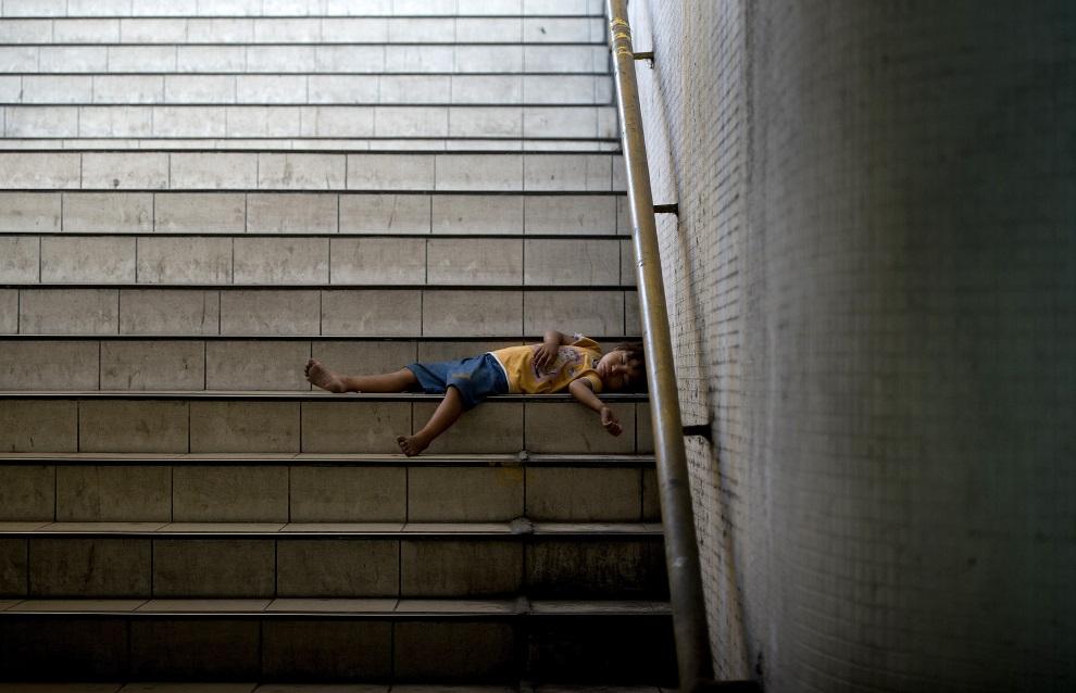 10.FILIPINY, Manila, 25 czerwca 2014: Dziecko śpiące na schodach prowadzących do podziemnego przejścia. AFP PHOTO/NOEL CELIS