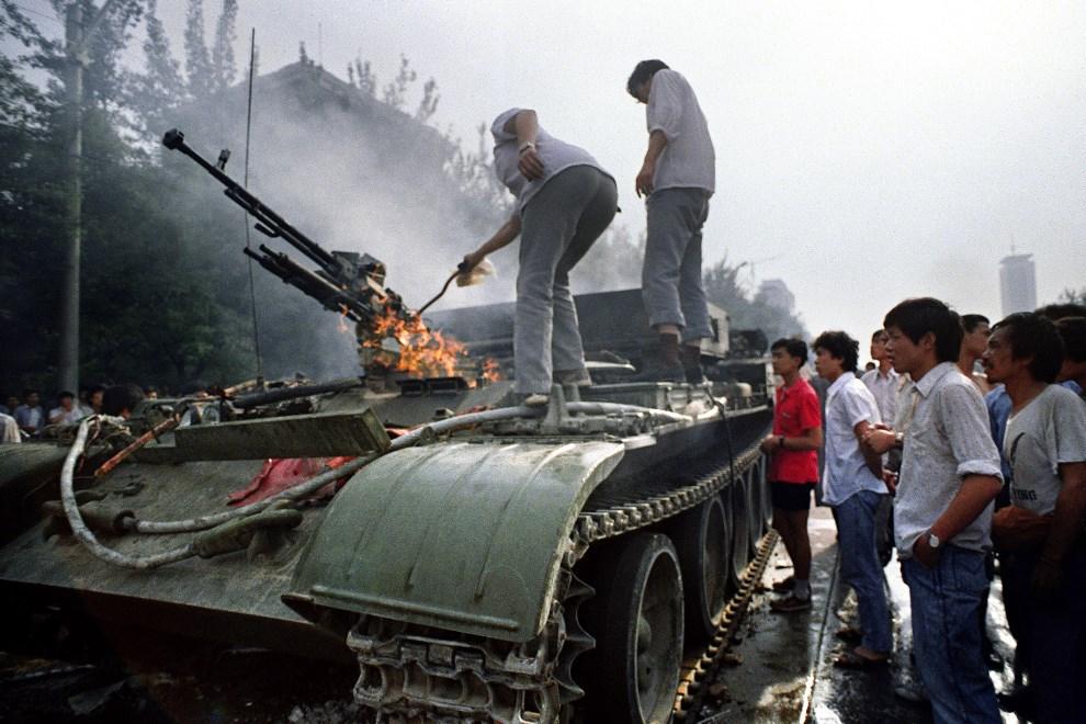 11.CHINY, Pekin, 4 czerwca 1989: Płonący transporter wojskowy, zniszczony podczas walk na placu Tiananmen. AFP PHOTO/FILES/TOMMY CHENG