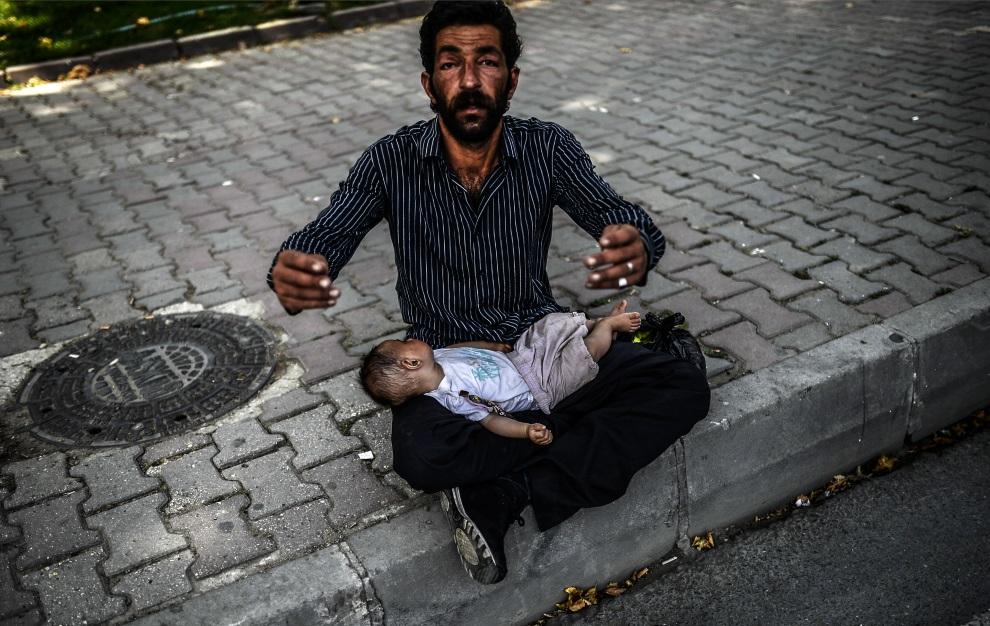 11.TURCJA, Stambuł, 19 czerwca 2014: Syryjski uchodźca z dzieckiem, żebrzący na ulicy. AFP PHOTO/BULENT KILIC
