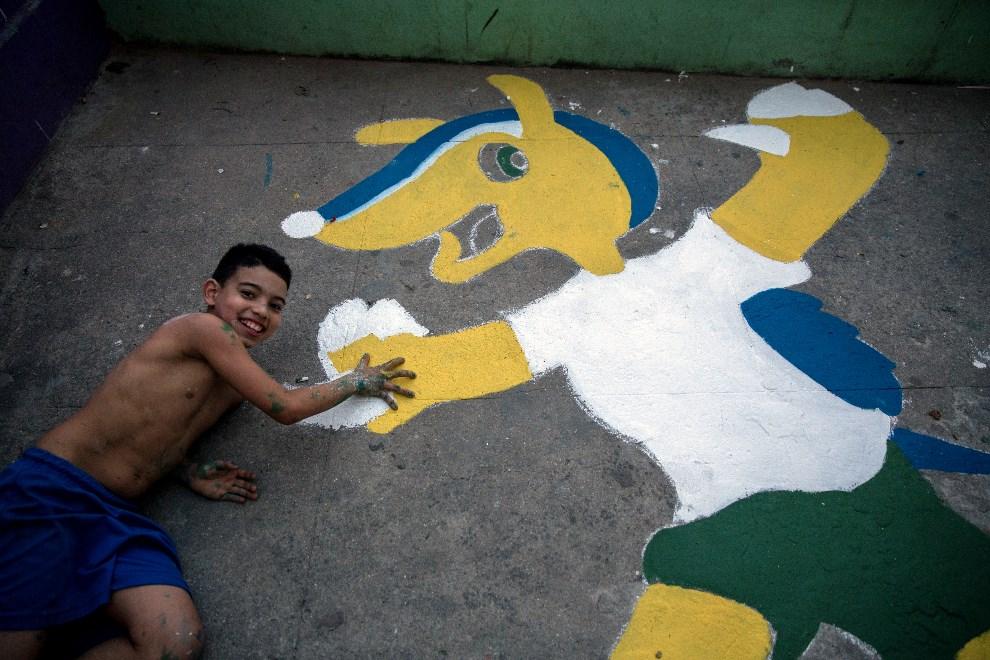 """13.BRAZYLIA, Rio de Janeiro, 7 czerwca 2014: Chłopiec przybija """"piątkę"""" z namalowaną maskotką zbliżającego się Mundiallu. AFP PHOTO / YASUYOSHI CHIBA"""