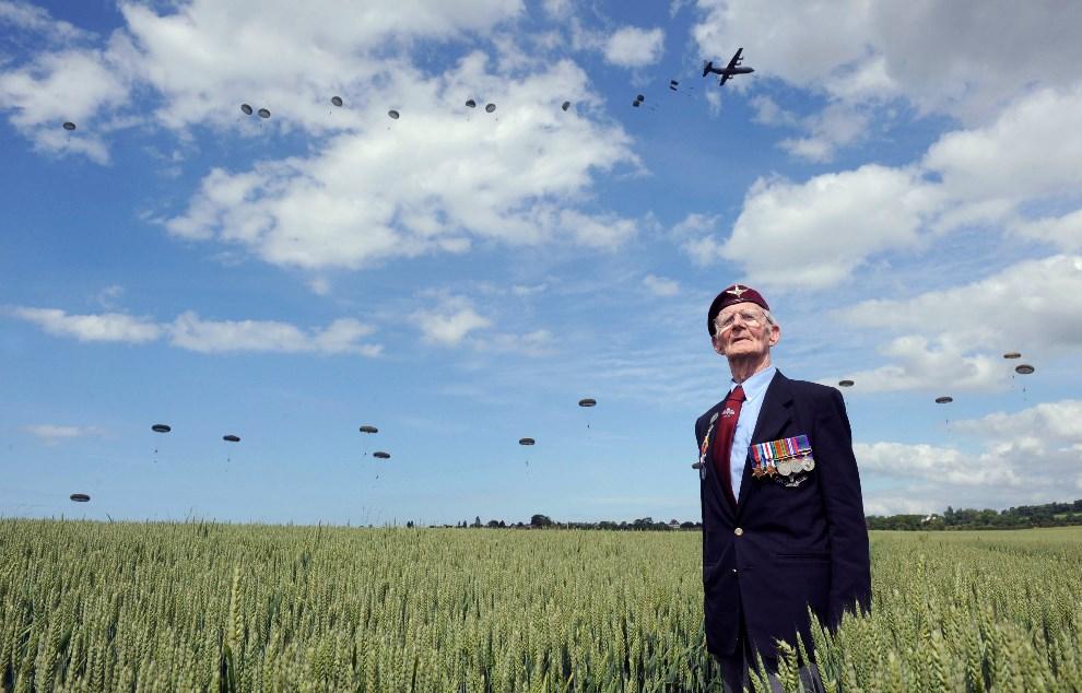 13.FRANCJA, Ranville, 5 czerwca 2014: Weteran z czasów II wojny światowej, Frederick Glover, na tle lądujących spadochroniarzy. AFP PHOTO / THOMAS BREGARDIS