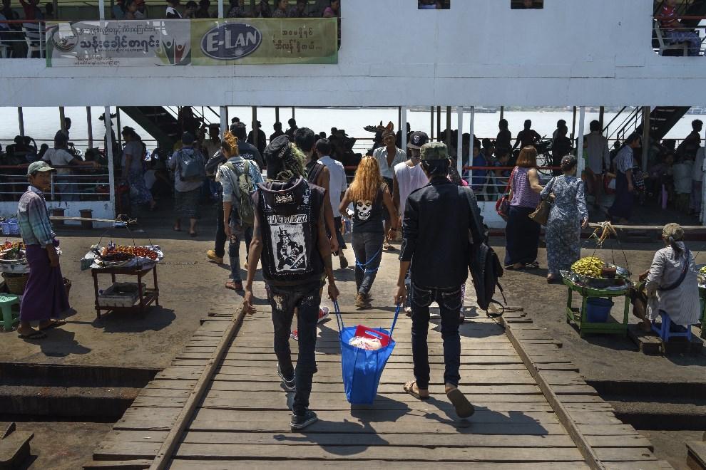 13.MJANMA, Rangun, 9 marca 2014: Członkowie lokalnego zespołu punkowego wnoszą żywność na pokład promu. (Foto: Getty Images/Getty Images)