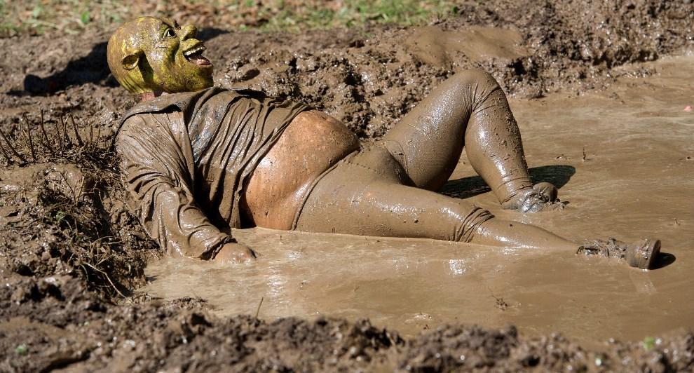 """14.NIEMCY, Hergisdorf, 9 czerwca 2014: Uczestnik zabawy nazywanej """"brudną świnką"""", w masce Shreka. AFP PHOTO / DPA/ PETER ENDIG /"""