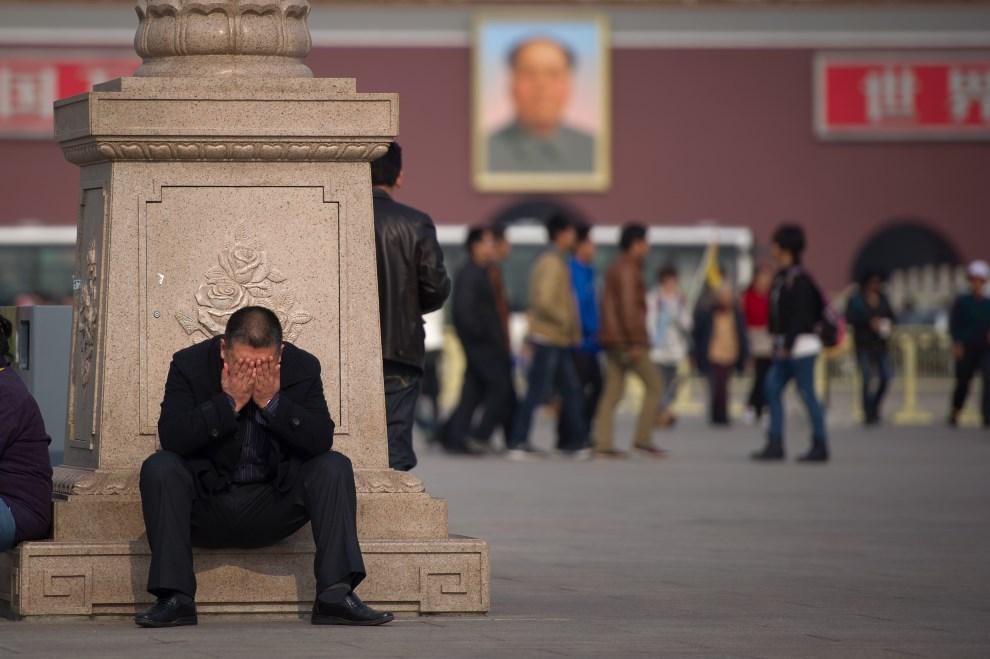 14.CHINY, Pekin, 9 listopada 2012: Mężczyzna odpoczywający na placu Tiananmen. AFP PHOTO / Ed Jones