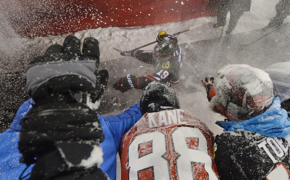 """14.USA, Chicago, 1 marca 2014: Jonathan Toews z Chicago Blackhawks przybija """"piątki"""" z kibicami w drodze do szatni. (Foto: Brian Kersey/Getty Images)"""