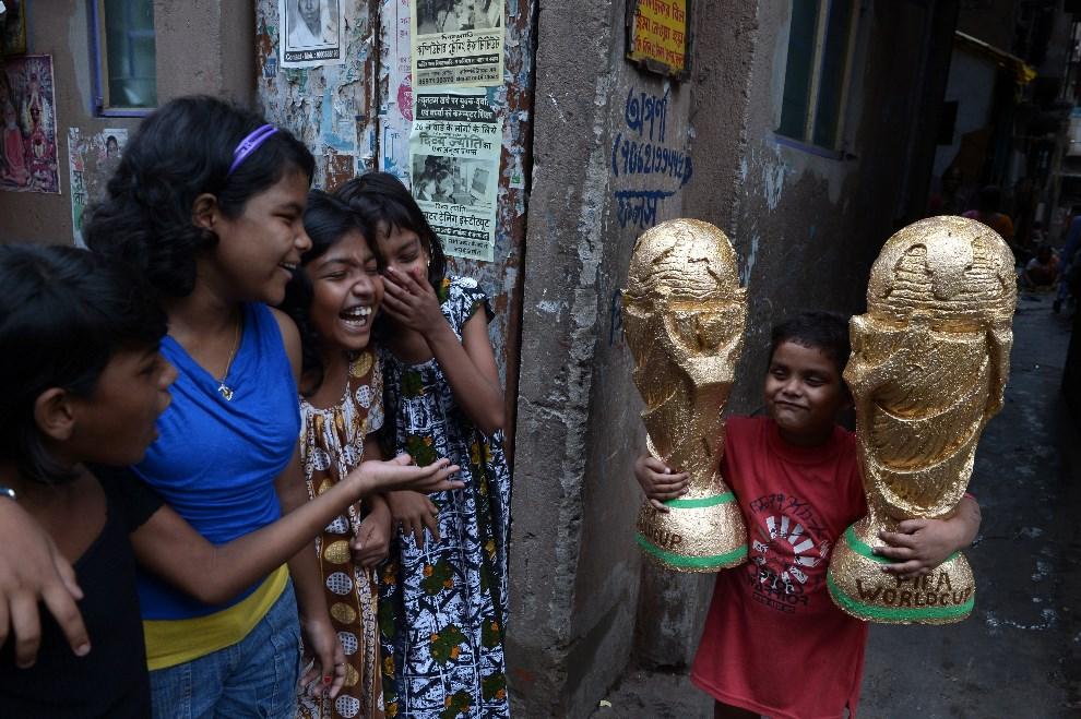 """16.INDIE, Kolkata, 18 czerwca 2014: Chłopiec z dwoma """"replikami"""" trofeum dla mistrzów świata. AFP PHOTO/ Dibyangshu Sarkar"""