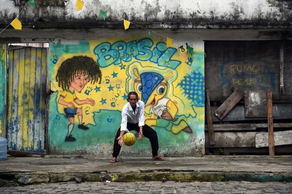 17. BRAZYLIA, Porto Seguro, 28 czerwca 2014: Brazylijczyk grający w piłkę na ulicy. AFP PHOTO / ANNE-CHRISTINE POUJOULAT