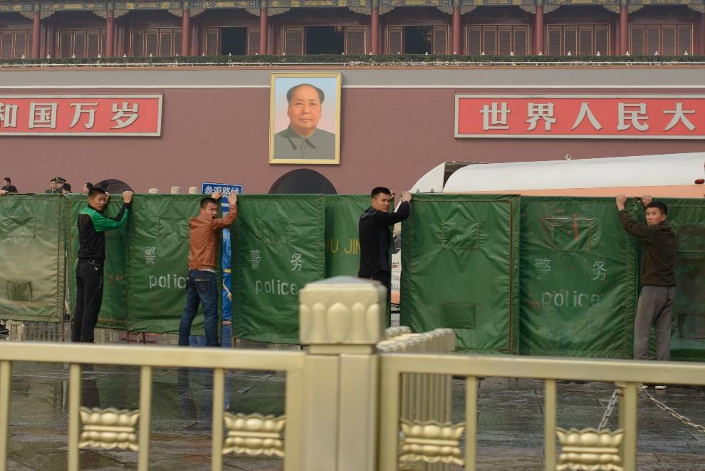 18.CHINY, Pekin, 28 października 2013: Policjanci w cywilu zasłaniają miejsce wypadku na placu Tiananmen. AFP PHOTO / Ed Jones