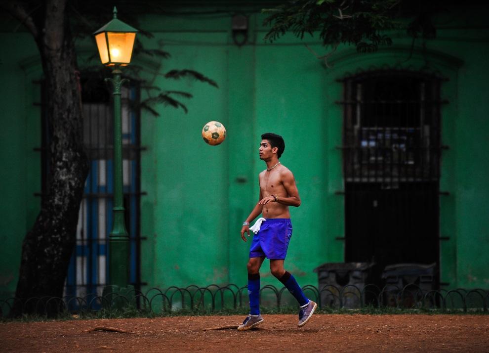 18. KUBA, Hawana, 27 czerwca 2014: Chłopak grający w piłkę na ulicy. AFP PHOTO/YAMIL LAGE