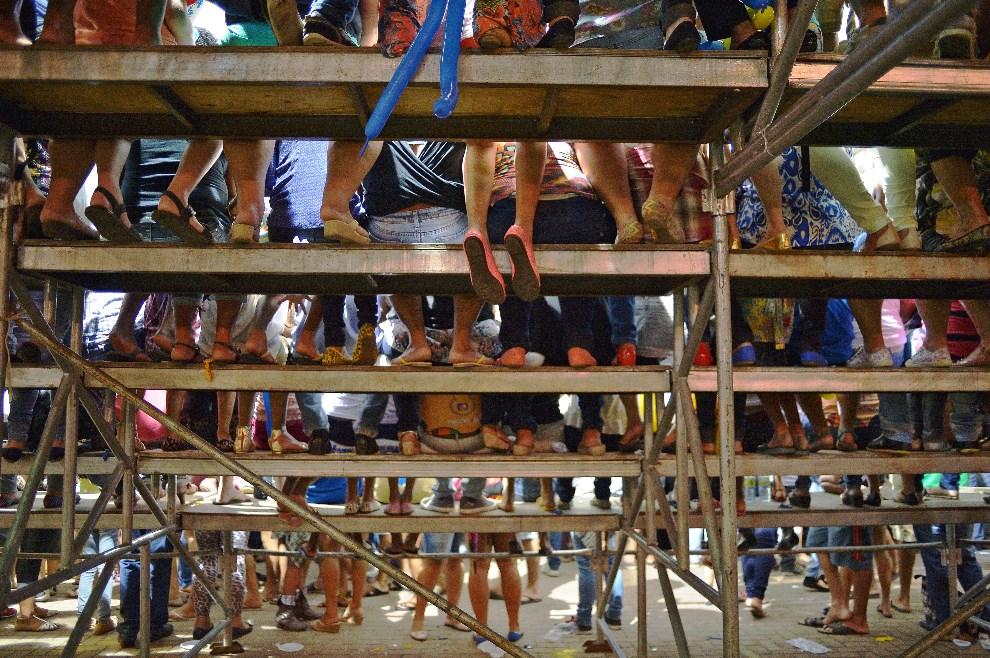 19.BRAZYLIA, Maceió, 18 czerwca 2014: Ludzie obserwujący występ piłkarski w pobiliżu miejsca zakwaterowania reprezentacji Ghany. AFP PHOTO/Carl de Souza