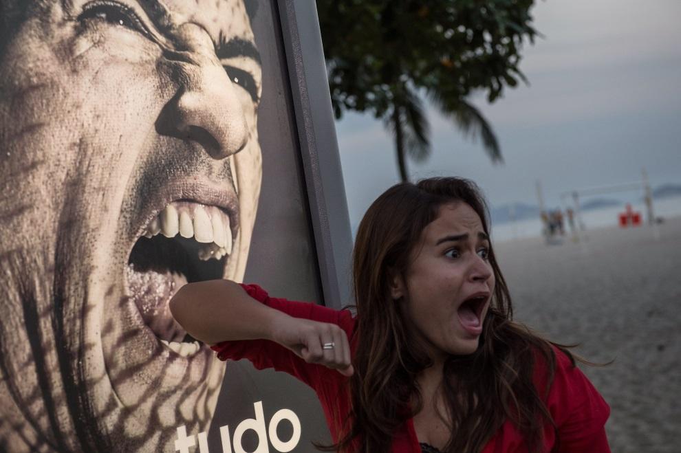 1. BRAZYLIA, Rio de Janeiro, 26 czerwca 2014: Turystka przed reklamą z wizerunkiem Luisa Suareza. AFP PHOTO / YASUYOSHI CHIBA