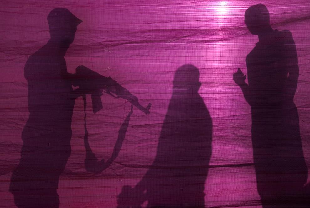 1.STREFA GAZY, 19 czerwca 2014: Członkowie Hamasu za parawanem osłaniającym miejsce eksplozji izraelskiej bomby lotniczej. AFP PHOTO/ MOHAMMED ABED