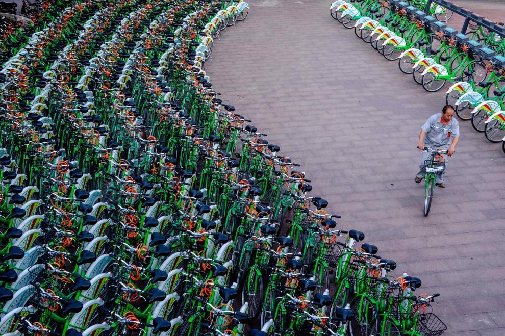 21.CHINY, Pekin, 14 czerwca 2014: Mężczyzna wypożyczający jeden z rowerów miejskich. AFP PHOTO