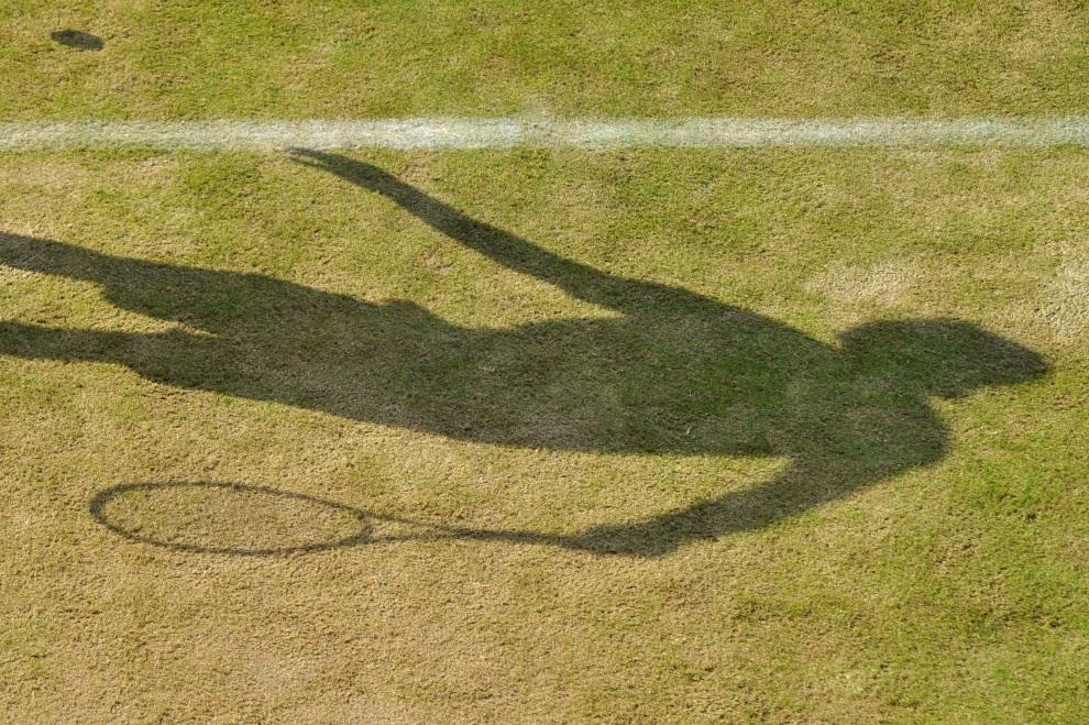 22.WIELKA BRYTANIA, Wimbledon, 24 czerwca 2014: Cień Maleka Jaziria serwującego piłkę. AFP PHOTO / GLYN KIRK