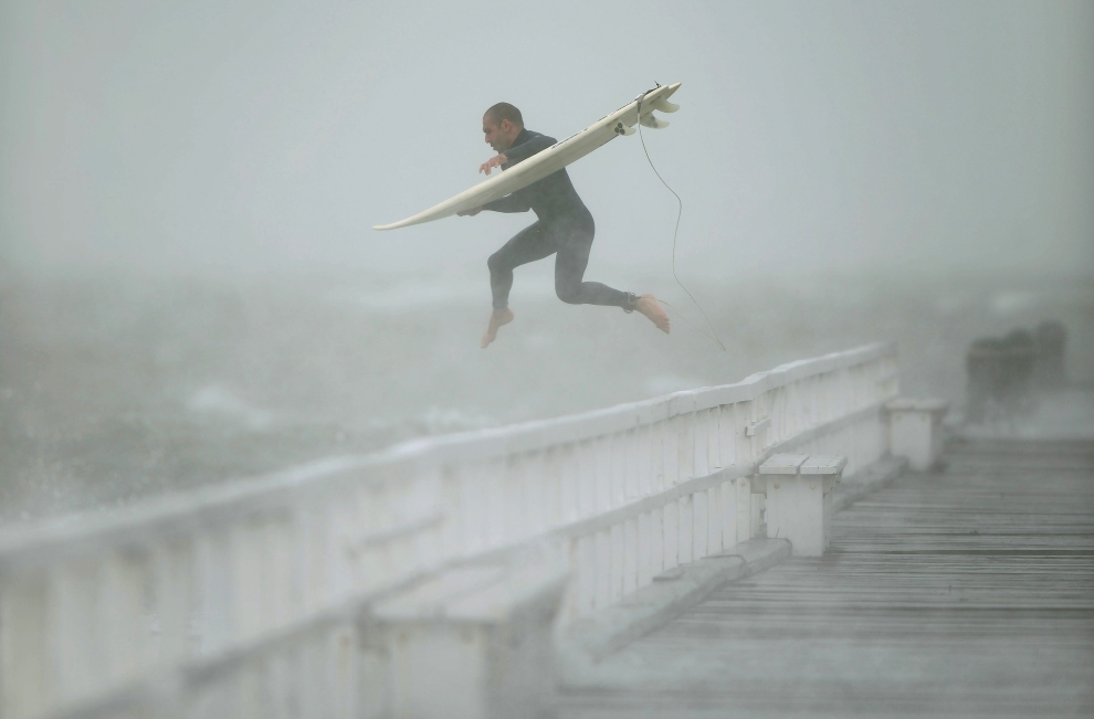 25.AUSTRALIA, Melbourne, 24 czerwca 2014:  Surfer skaczący do wody w zatoce Port Phillip. AFP PHOTO / MAL FAIRCLOUGH
