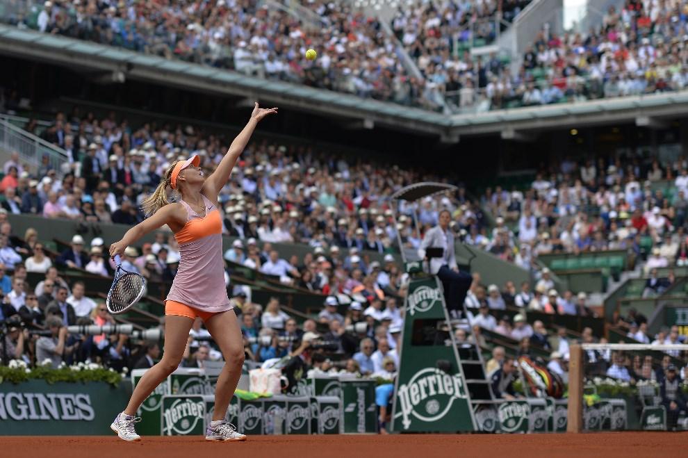 26.FRANCJA, Paryż, 5 czerwca 2014:  Maria Sharapova serwuje piłkę podczas pojedynku z  Eugenie Bouchard. AFP PHOTO / MIGUEL MEDINA