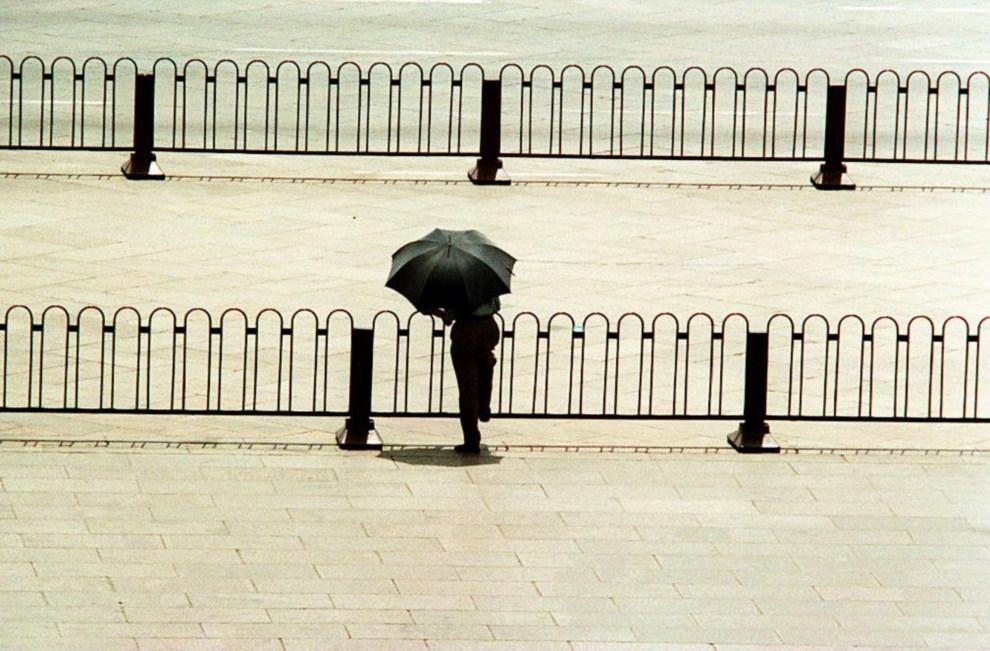 27.CHINY, Pekin, 4 czerwca 1994: Policjant w cywilu chroni się przed słońcem. AFP