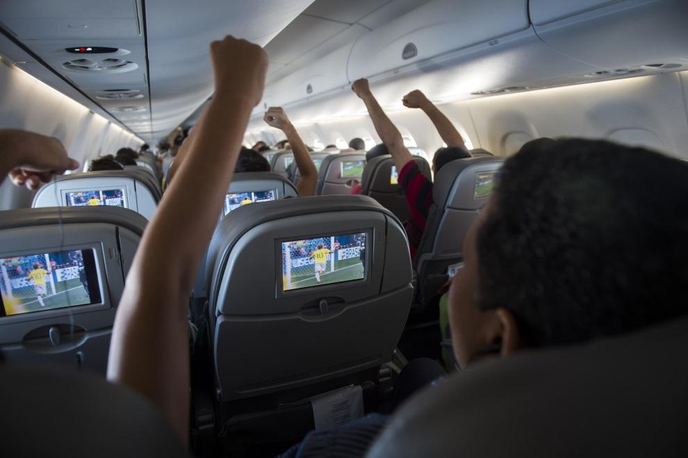 27. BRAZYLIA, 23 czerwca 2014: Pasażerowie samolotu cieszą się z gola strzelonego przez Neymara w meczu z Kamerunem. AFP PHOTO / ODD ANDERSEN