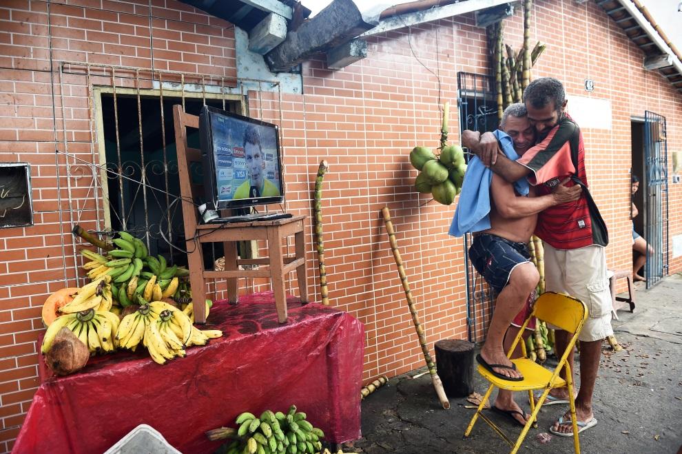 28. BRAZYLIA, Porto Seguro, 28 czerwca 2014: Uliczny sprzedawca bananów cieszy się ze awansu Brazylii do dalszej fazy rozgrywek. AFP PHOTO / ANNE-CHRISTINE  POUJOULAT
