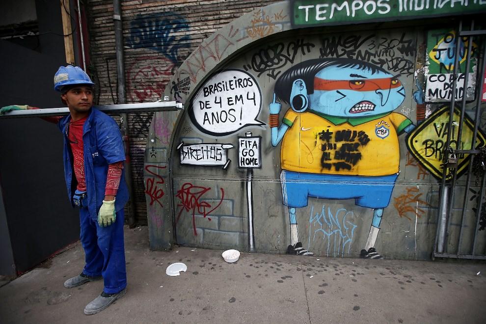 29.BRAZYLIA, Sao Paulo, 10 czerwca 2014: Pracownik budowy na tle graffiti. (Foto: Mario Tama/Getty Images)
