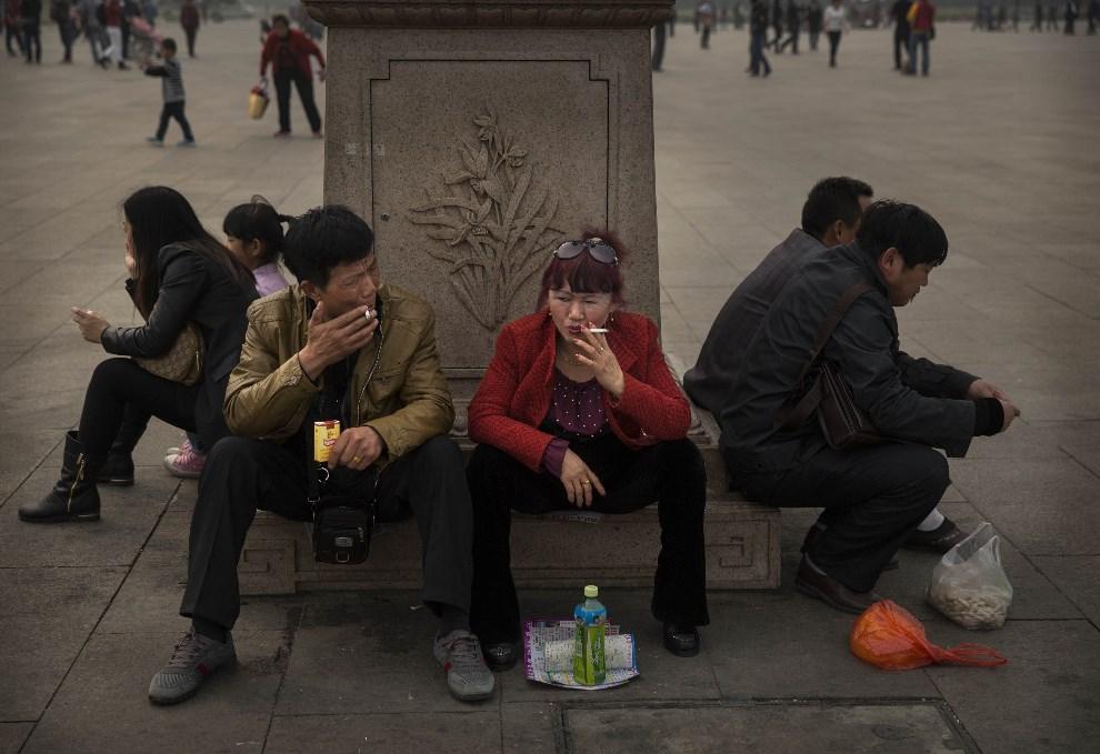 35.CHINY, Pekin, 26 marca 2014: Ludzie odpoczywający nap placu Tiananmen. (Foto: Kevin Frayer/Getty Images)