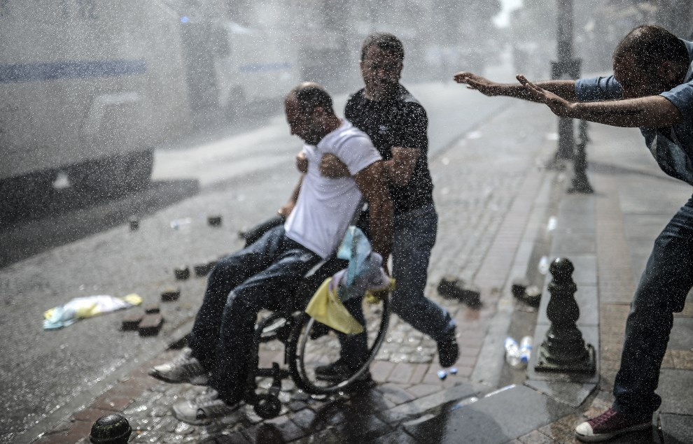 3.TURCJA, Stambuł, 8 czerwca 2014: Ludzie pomagają mężczyźnie na wózku w trakcie starć Kurdów z policją. AFP PHOTO / BULENT KILIC