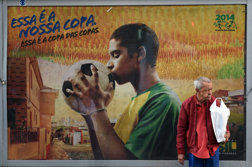 3.BRAZYLIA, Belo Horizonte, 9 czerwca 2014: Mężczyzna na tle plakatu reklamującego mundial. AFP PHOTO / Martin BERNETTI