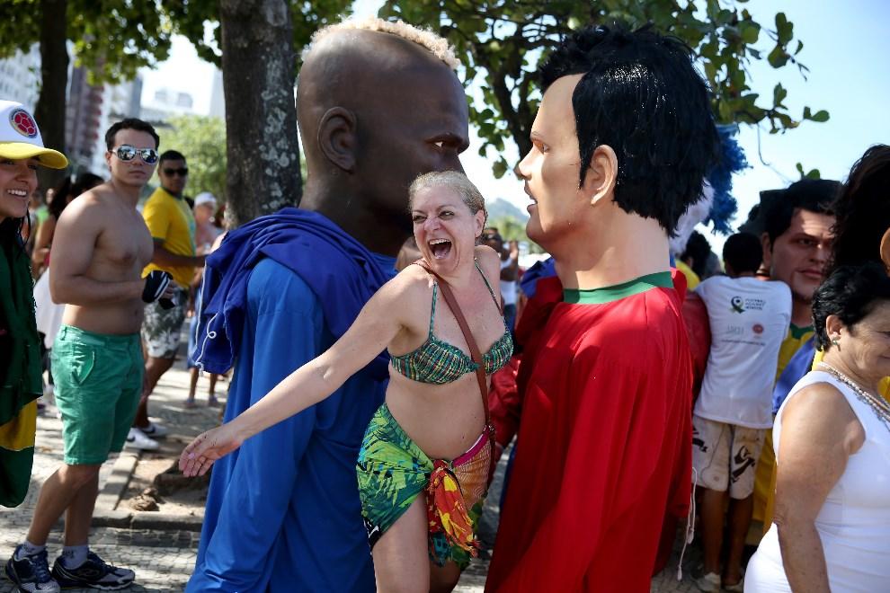 4.BRAZYLIA, Rio de Janeiro, 8 czerwca 2014: Kobieta między lalkami z podobiznami zawodników występujących podczas mundialu. (Foto: Joe Raedle/Getty Images)
