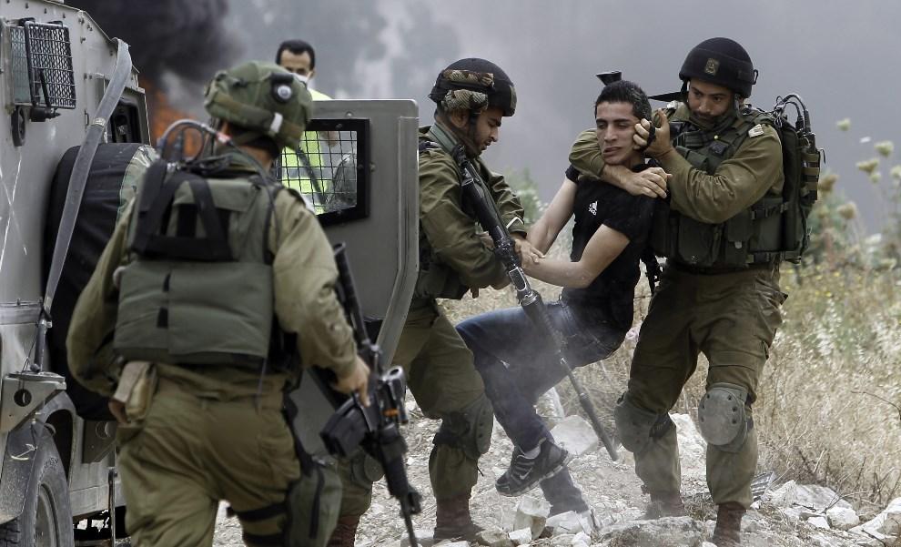 5.AUTONOMIA PALESTYŃSKA, Tulkarem, 31 maja 2014: Izraelscy żołnierze zatrzymują Palestyńczyka protestującego przeciw ekspansji terytorialnej Izraela. AFP PHOTO/JAAFAR ASHTIYEH
