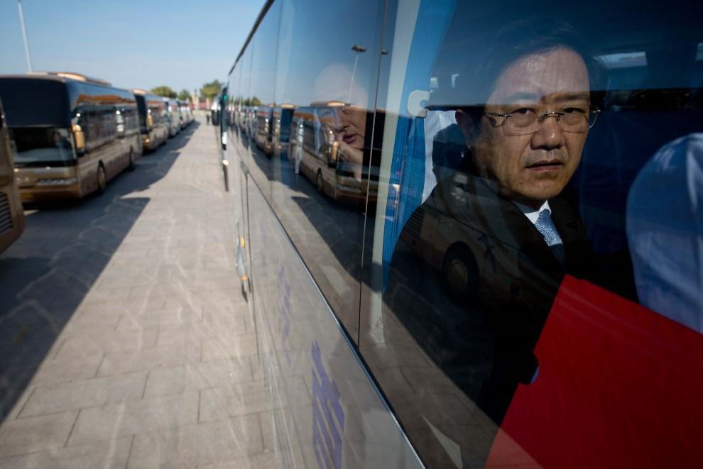 6.CHINY, Pekin, 14 listopada 2012: Delegaci partyjni oczekują na odjazd autobusów z placu Tiananmen. AFP PHOTO / Ed Jones