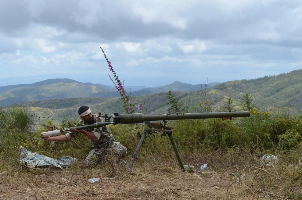 6.SYRIA, Latakia, 1 czerwca 2014: Rebeliant ładuje działo przeciwpancerne. AFP PHOTO / MAHMOUD TAHA