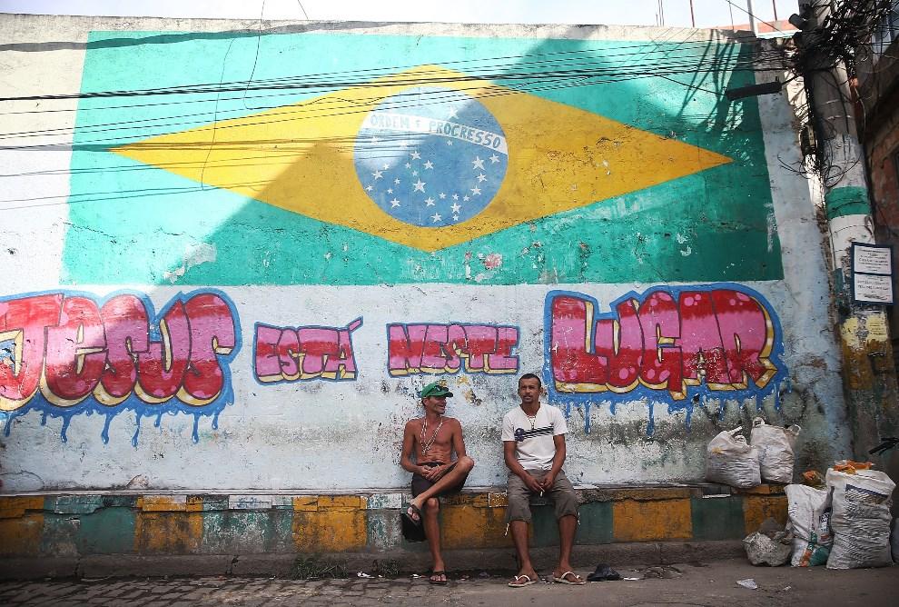 6.BRAZYLIA, Rio de Janeiro, 7 czerwca 2014: Mężczyźni na tle muralu u wejścia do faweli Complexo da Mare. (Foto: Mario Tama/Getty Images)