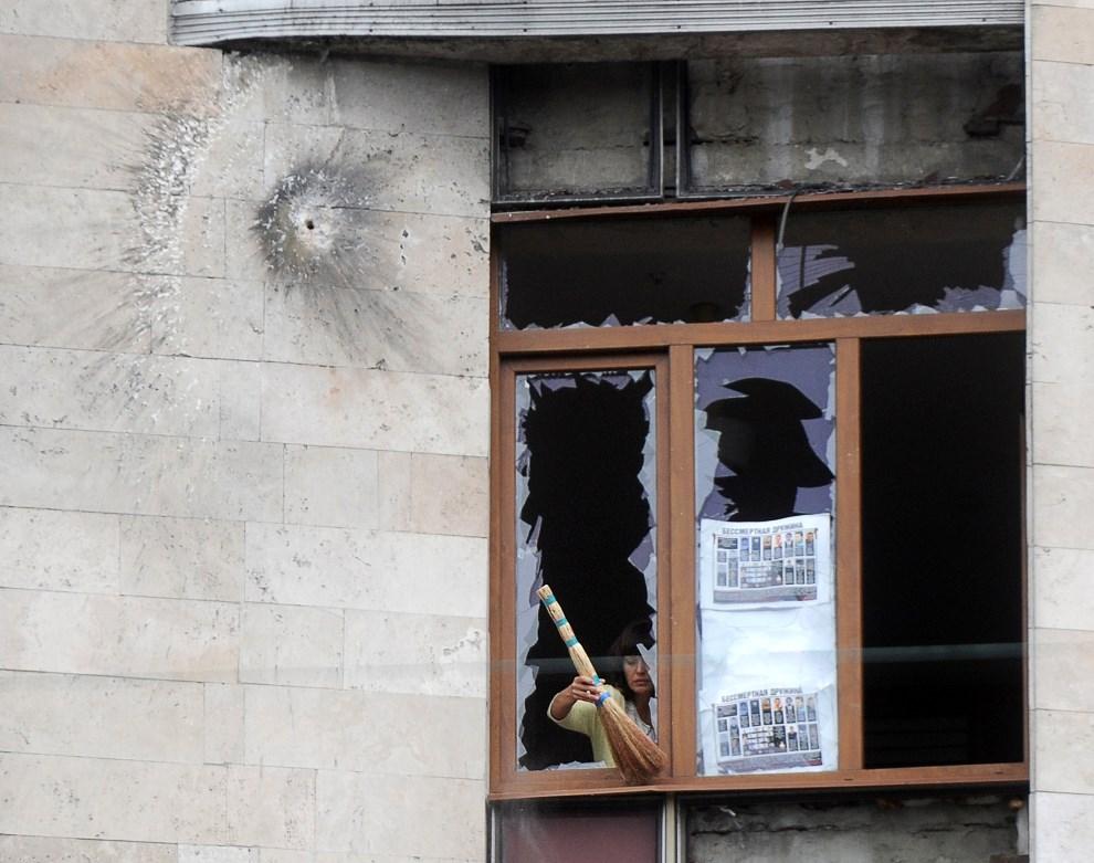 7.UKRAINA, Donieck, 2 czerwca 2014: Kobieta usuwa szkło z okna po nocnych walkach. AFP PHOTO/ VIKTOR DRACHEV