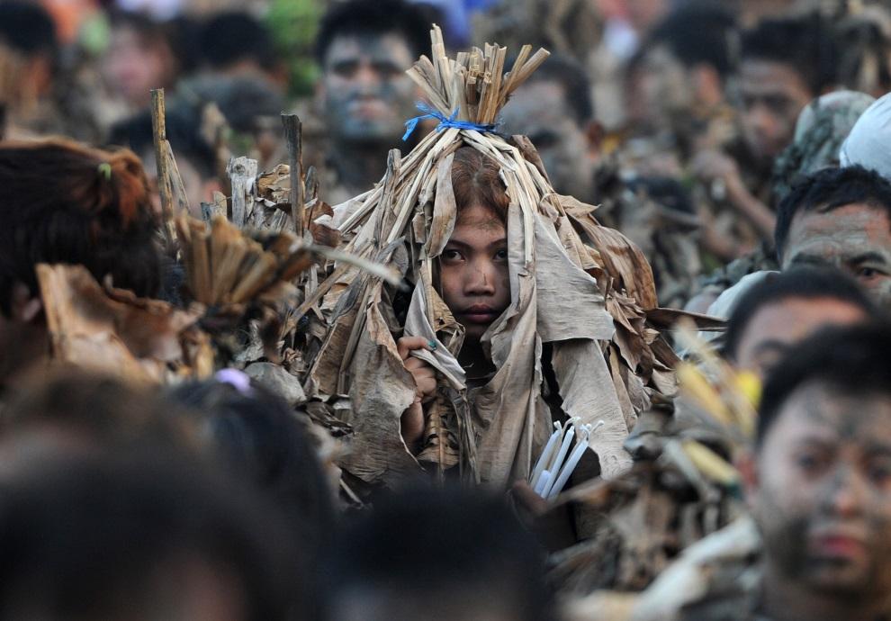 8.FILIPINY, Aliaga, 24 czerwca 2014: Ludzie ubrudzeni błotem i okryci liśćmi bananowców uczestniczą w mszy z okazji święta ku czci Jana Chrzciciela. AFP PHOTO /   TED ALJIBE