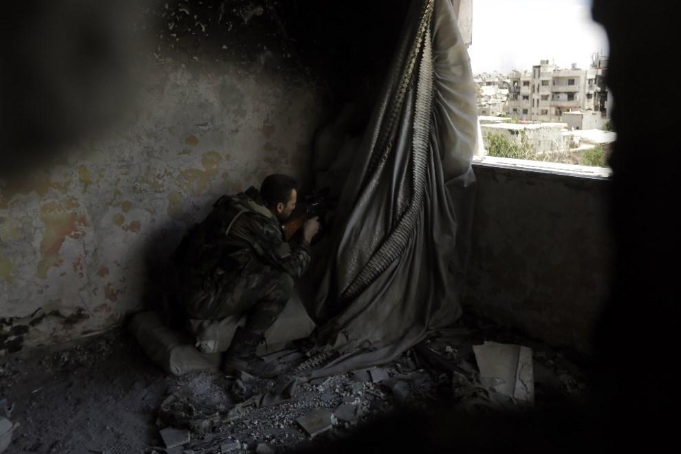 8.SYRIA, Damaszek, 2 czerwca 2014: Syryjski żołnierz na pozycji w jednym ze zniszczonych budynków w centrum miasta. AFP PHOTO/JOSEPH EID