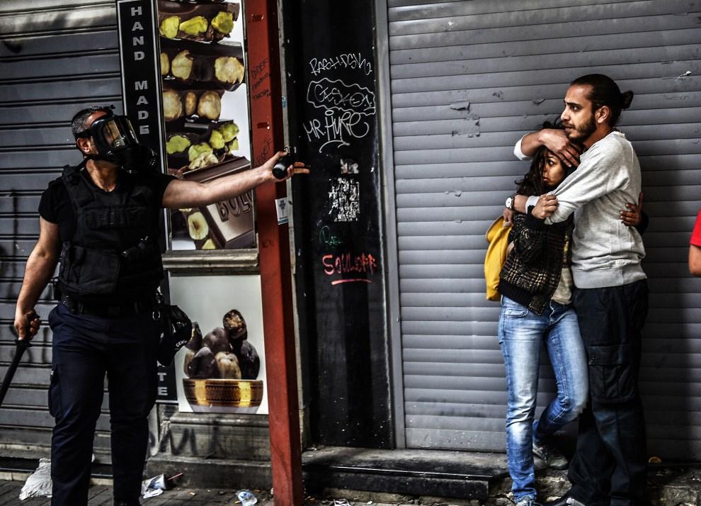 9.TURCJA, Stambuł, 31 maja 2014: Policjant i ludzie protestujący w rocznicę zamieszek w parku Gezi. AFP PHOTO / BULENT KILIC