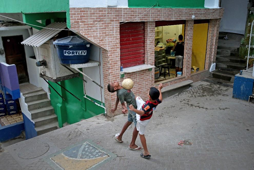 9.BRAZYLIA, Rio de Janeiro, 8 czerwca 2014: Chłopcy grający w piłę na ulicy w faweli Santa Marta. (Foto: Joe Raedle/Getty Images)