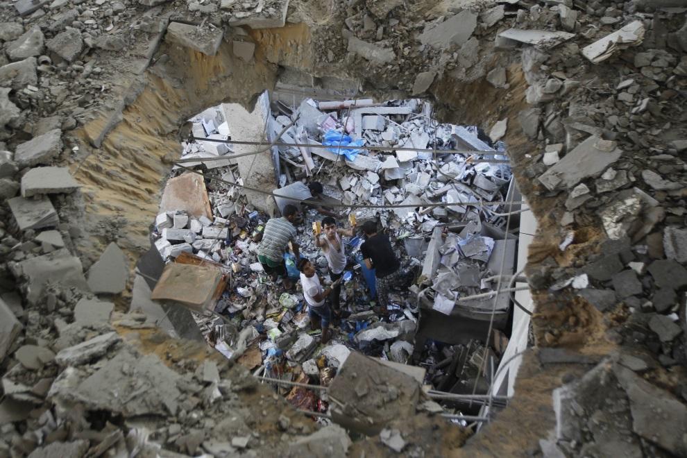 10.AUTONOMIA PALESTYŃSKA, Rafah, 15 lipca 2014: Palestyńczycy przeszukują gruzy budynku zniszczonego w wyniku nalotu. AFP PHOTO / SAID KHATIB