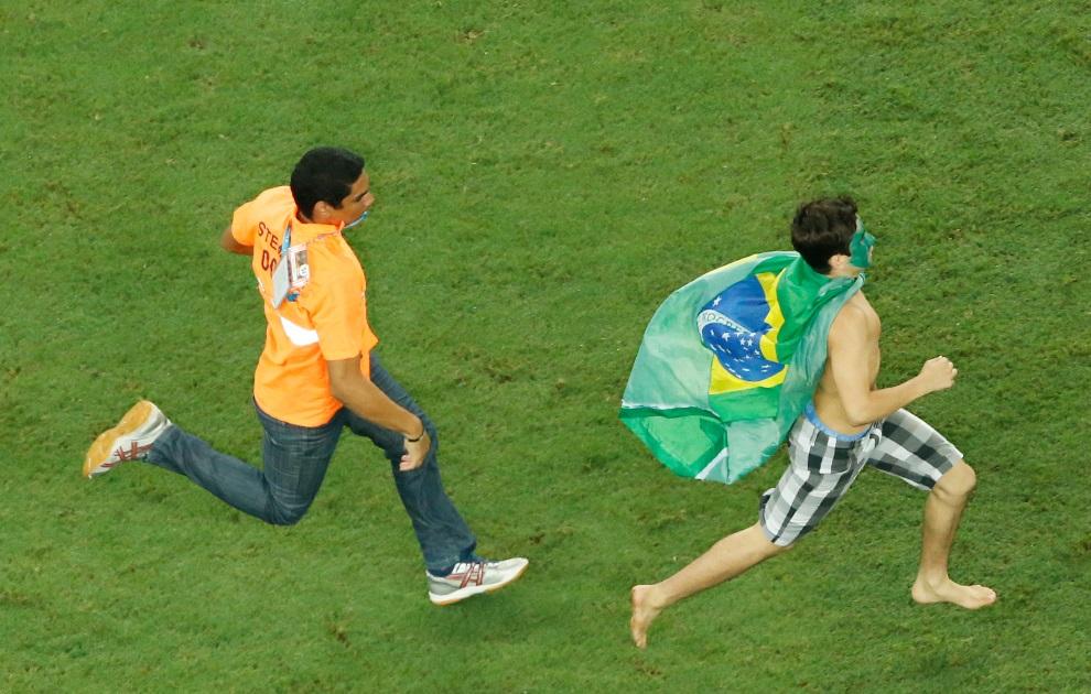 14.BRAZYLIA, Fortaleza, 4 lipca 2014: Kibic, który wtargnął na boisko, ucieka przed stewartem. AFP PHOTO / POOL / FABRIZIO BENSCH