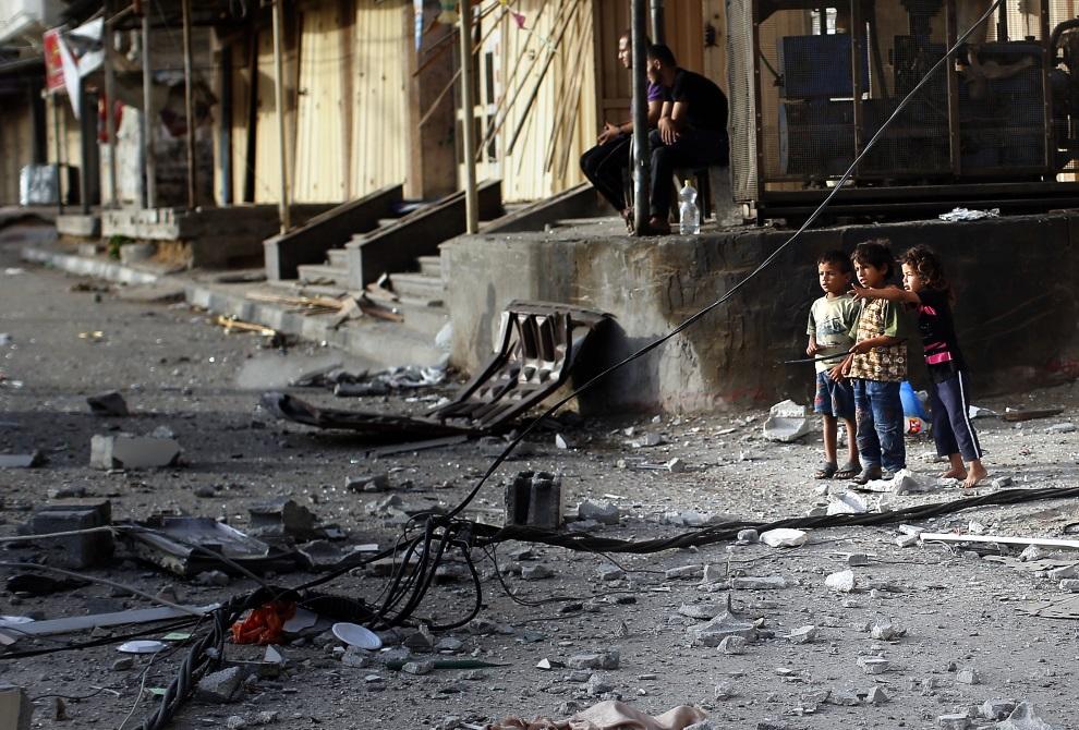 15.STREFA GAZY, obóz Nuseirat, 12 lipca 2014: Fragmenty zbombardowanego meczetu rozrzucone po przyległych ulicach. AFP PHOTO/THOMAS COEX