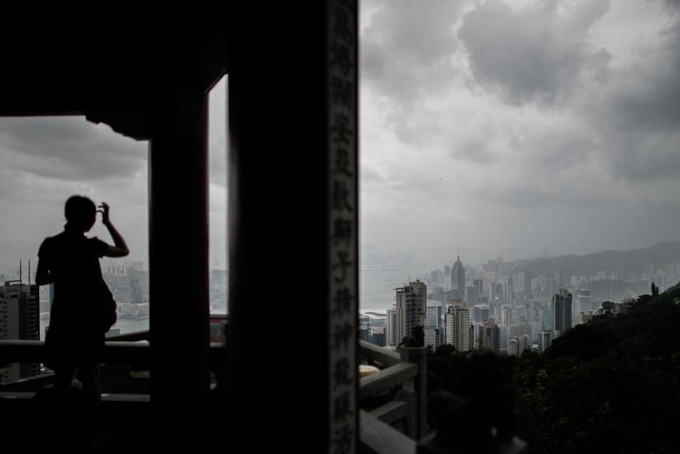 17.CHINY, Hongkong, 17 lipca 2014: Kobieta obserwuje zbliżający się tajfun. AFP PHOTO / Philippe Lopez